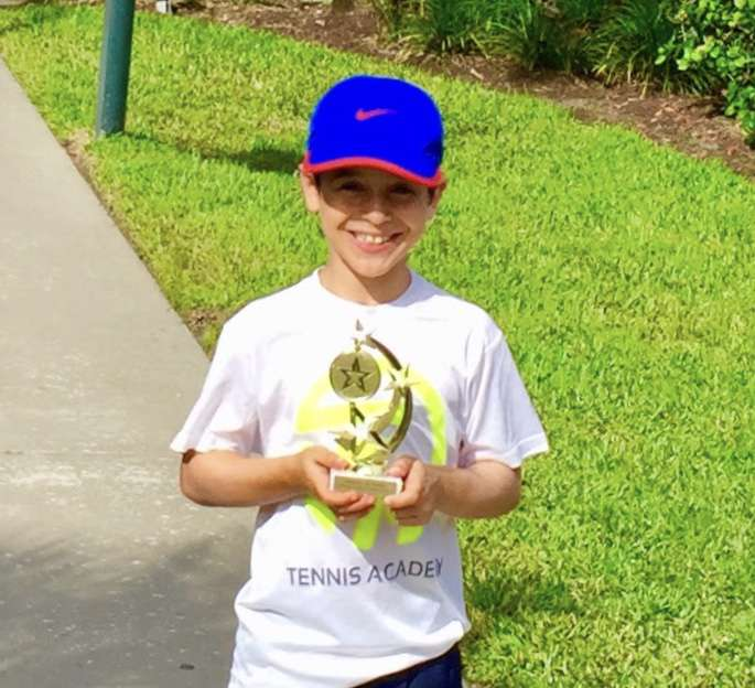 Young tennis player holding trophy